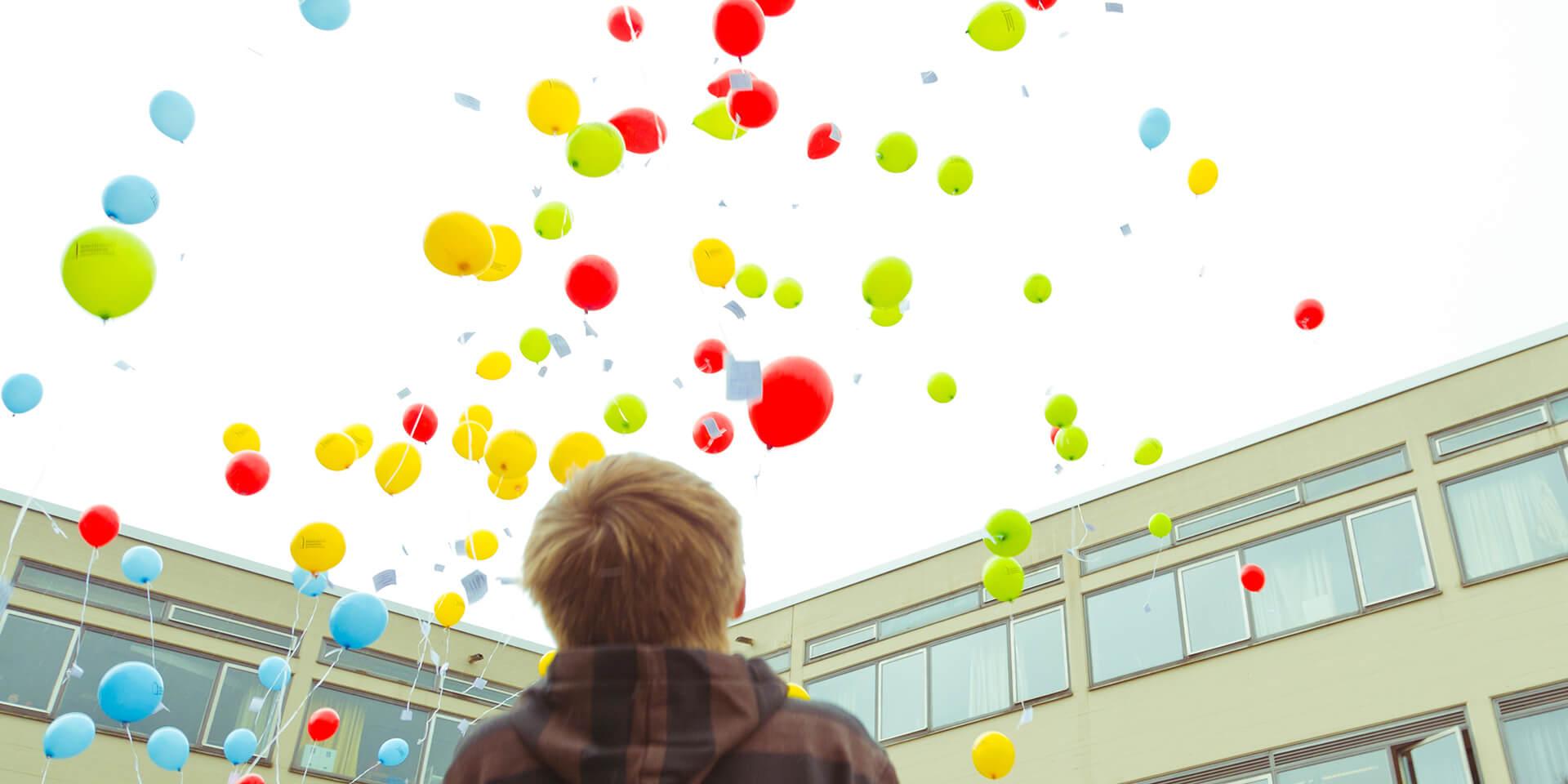 Ein Junge blickt in den Himmel voller Luftballons