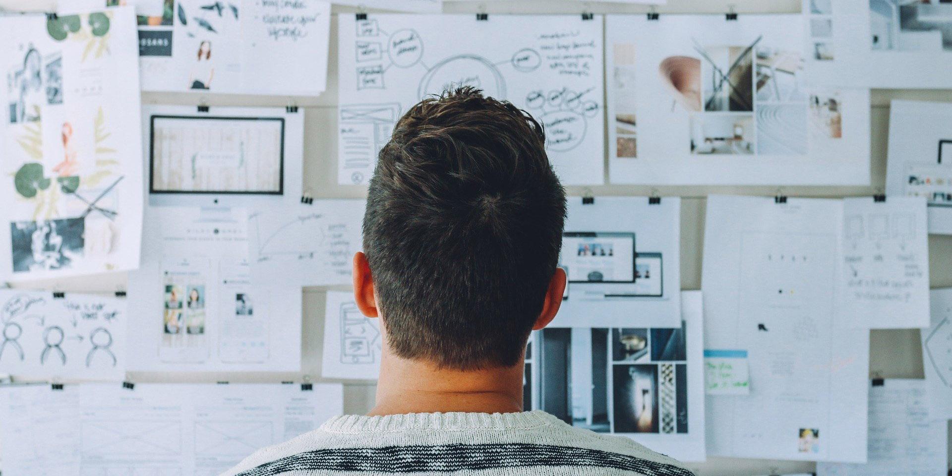 Ein Mann steht vor einer mit Notizen gefüllten Magnetwand im Büro.
