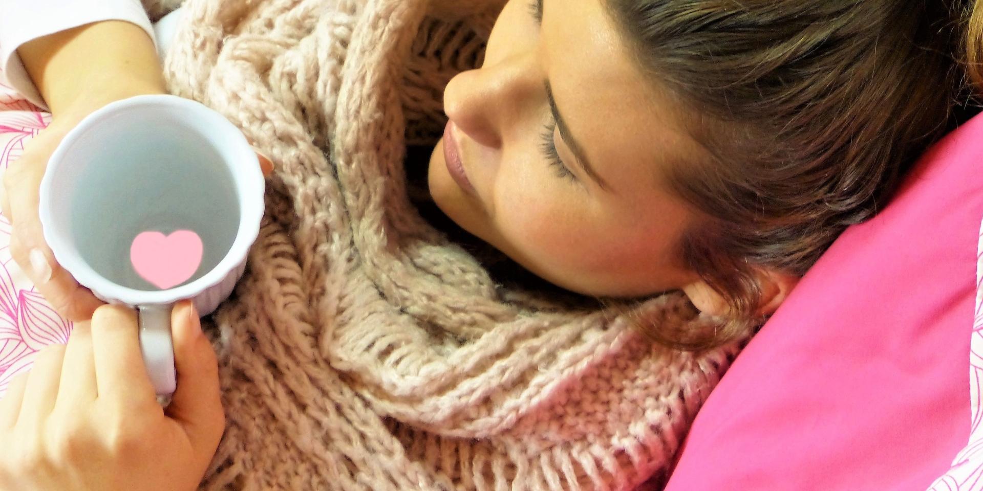 Junge Frau mit Schal und einer Tasse Tee